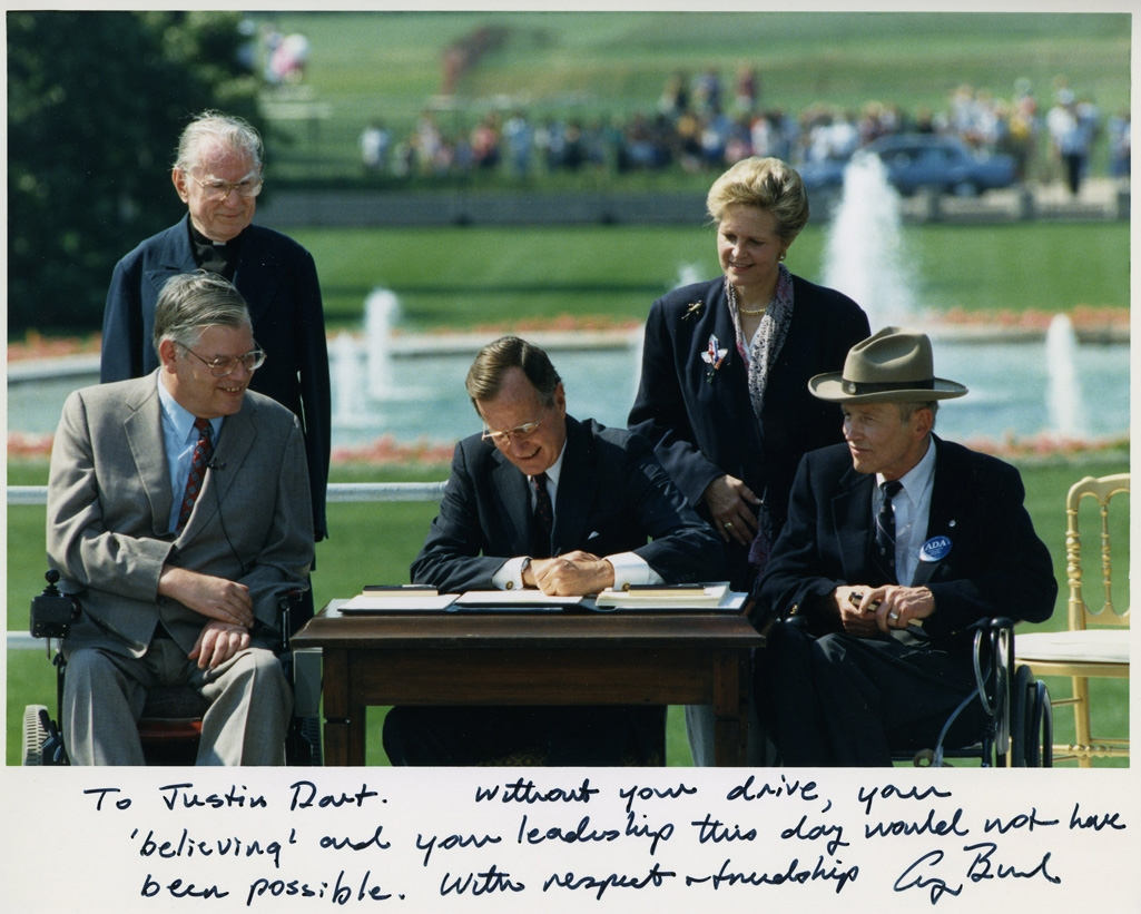 56942be9feb451344a7c1600_Photo_of_President_George_H._W._Bush_signing_the_Americans_with_Disabilities_Act_inscribed_to_Justin_Dart,_Jr.,_1990